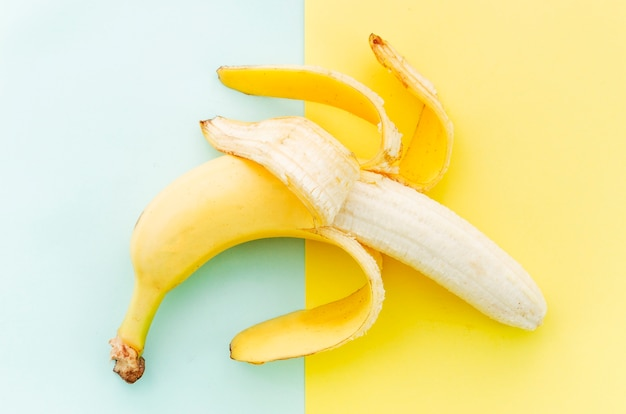 Cleared banana on colored surface Free Photo