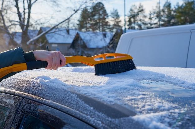 ブラシで車の屋根から雪を取り除く Premium写真