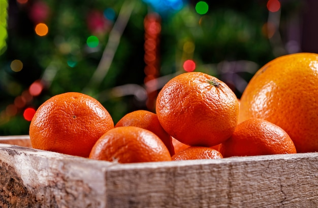 Clementines or tangerines in the box on christmas lights. Premium Photo