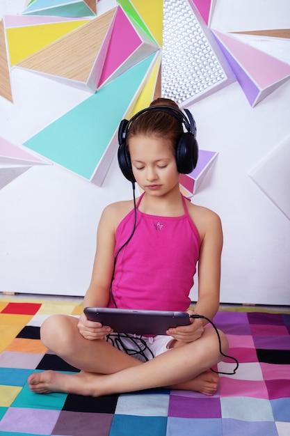 Умная девочка с планшета в комнате изучения. Premium Фотографии