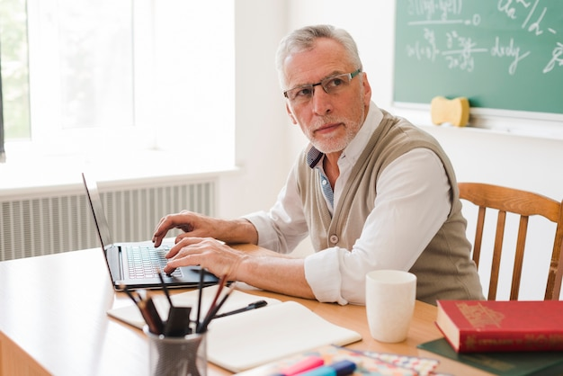 Clever old professor using laptop in classroom Free Photo