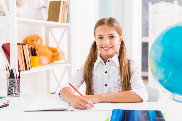 Clever schoolgirl sitting at desk Free Photo