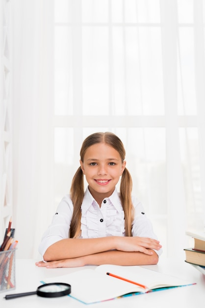 Clever schoolgirl sitting ready to study Free Photo