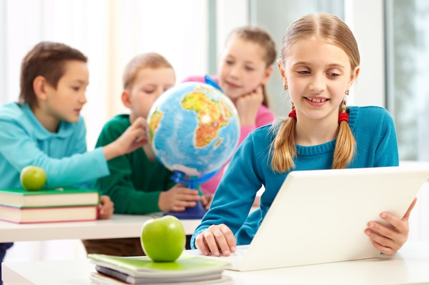 Clever schoolgirl with laptop in class Free Photo