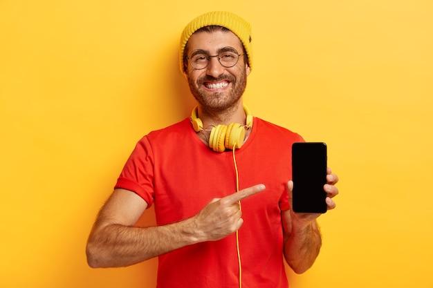 このボタンをクリックします。トレンディな帽子と赤いtシャツで満足している男子生徒、スマートフォンデバイスで人差し指でポイント 無料写真