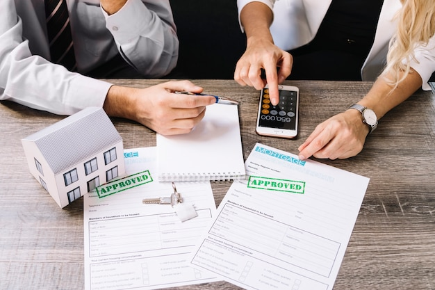 Client And Agent Calculating House Price Free Photo