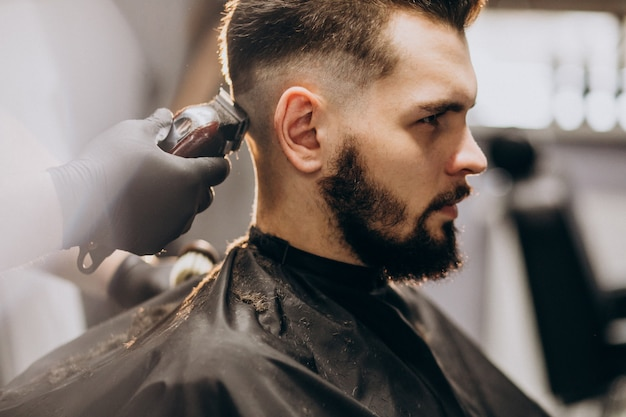 Client doing hair cut at a barber shop salon Free Photo