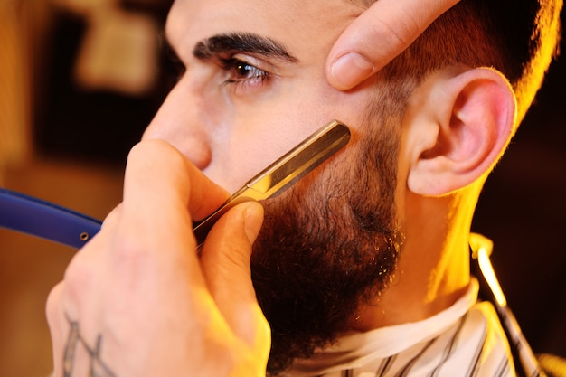 Client during beard shaving in barber shop Premium Photo