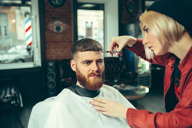Cliente durante la rasatura della barba nel negozio di barbiere. barbiere femminile al salone. parità dei sessi. donna nella professione maschile. Foto Gratuite