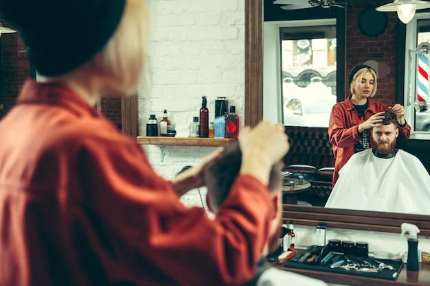 Cliente durante la rasatura della barba nel negozio di barbiere. barbiere femminile al salone. parità dei sessi Foto Gratuite