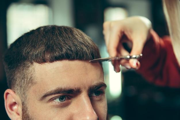 Клиент во время бритья бороды в парикмахерской. женский парикмахер в салоне. гендерное равенство. женщина в мужской профессии. Бесплатные Фотографии