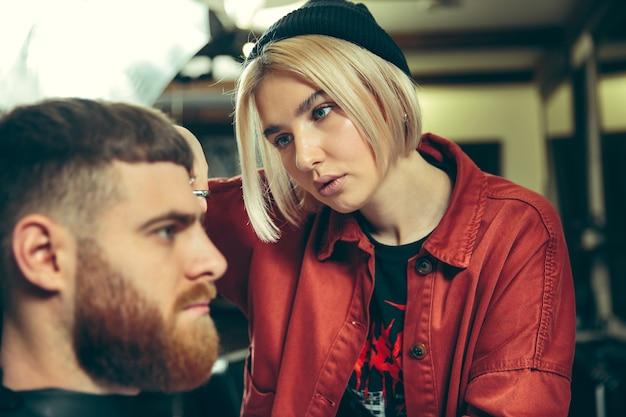 理髪店でひげを剃っている間のクライアント。サロンの女性理髪店。男女平等。男性の職業の女性。 無料写真