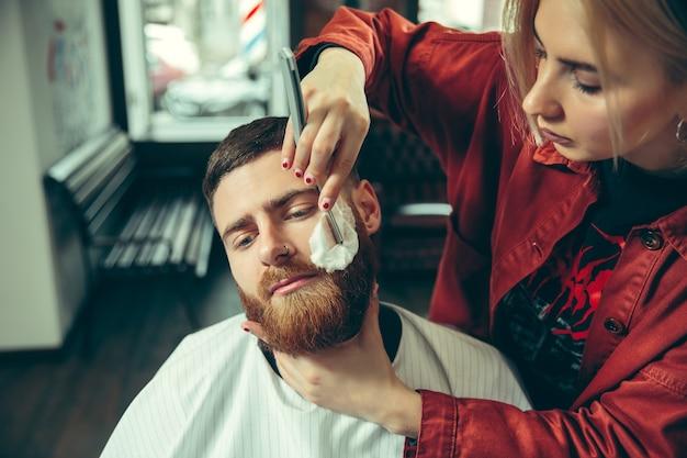 이발소에서 수염을 면도하는 동안 클라이언트. 살롱에서 여성 이발사. 남녀 평등. 남성 직업에있는 여자. 무료 사진