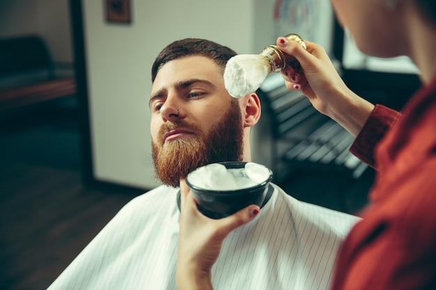 Клиент во время бритья бороды в парикмахерской. Бесплатные Фотографии