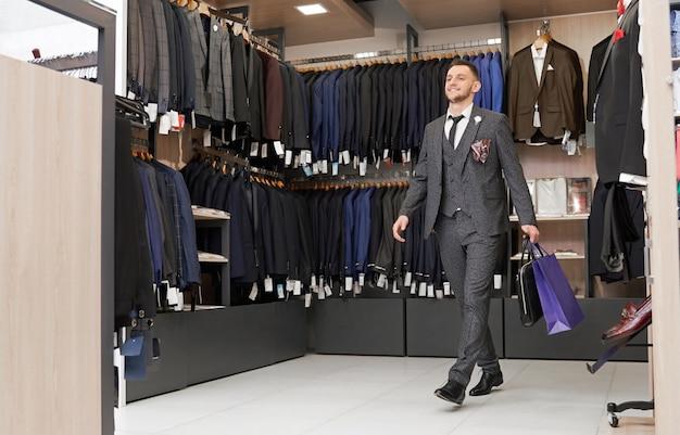 Клиент в костюме в бутике с сумками. Бесплатные Фотографии