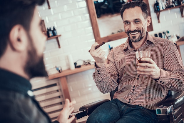Client is drinking whiskey in a barber shop Premium Photo