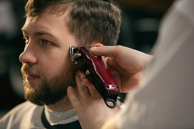 Cliente del maestro barbiere, stilista durante la cura e il nuovo look dell'acconciatura Foto Gratuite
