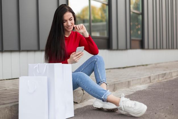 Cliente in camicia rossa che si siede e che utilizza il suo telefono cellulare Foto Gratuite