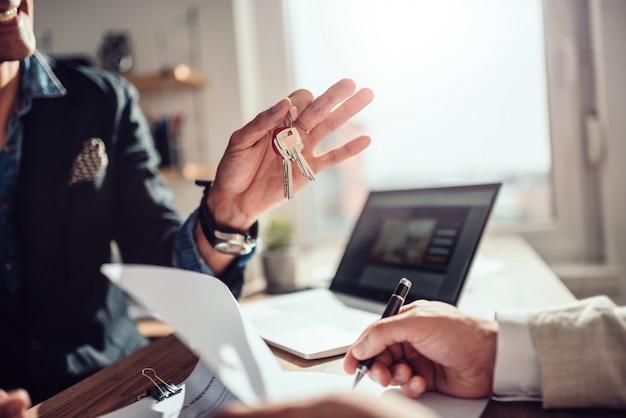 Клиент подписывает контракт, а агент по недвижимости держит ключи Premium Фотографии