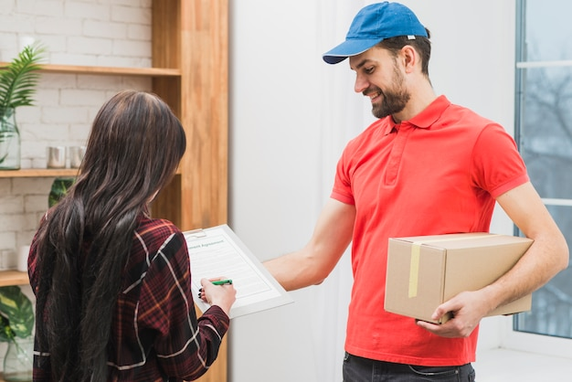 Client signing for parcel from courier Free Photo