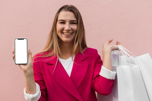 Cliente che indossa abiti di moda e che tiene la vista frontale del telefono cellulare Foto Gratuite