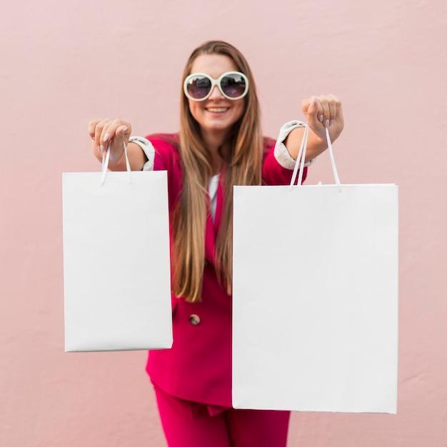 ショッピングバッグを示すファッションの服を着ているクライアント 無料写真