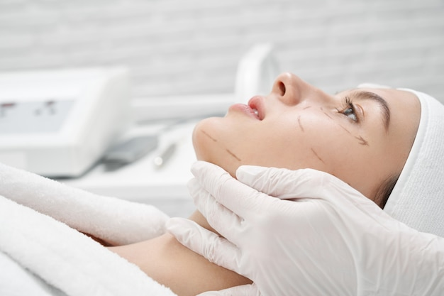 Client with markup on face visiting surgeon in clinic Premium Photo