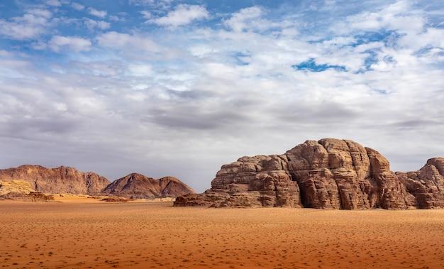 낮에는 흐린 하늘 아래 마른 풀이 가득한 사막의 절벽과 동굴 무료 사진