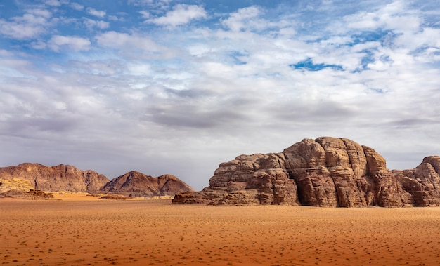 Cliffs and caves on a desert full of dry grass under a cloudy sky during daytime Free Photo