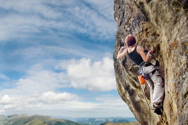 Climber climbing with rope and carbines on a big rocky wall Premium Photo