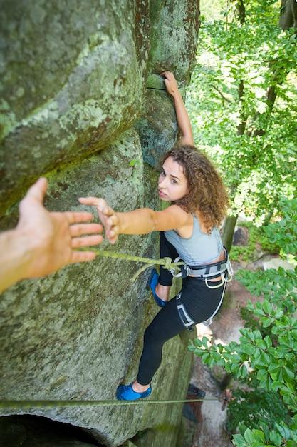 Climber helping female climber to reach a peak of mountain Premium Photo