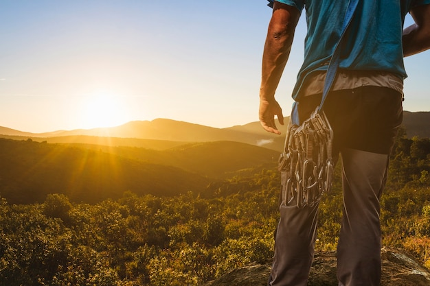 Climber looking out to a sunset landscape Free Photo