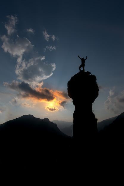 登山家は彼の手を上にして頂上を征服した後喜ぶ Premium写真