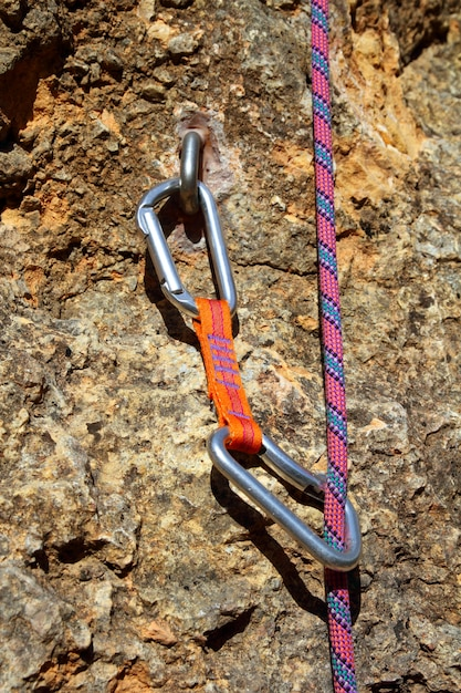 Climbing shackles and rope on a rock wal Premium Photo