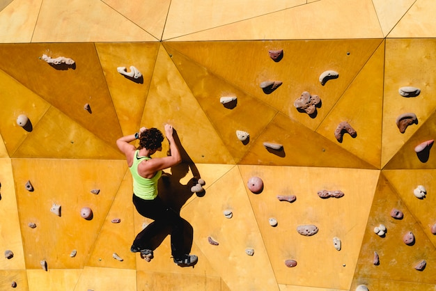 Climbing wall with strong woman in good shape doing exercise outdoors Premium Photo