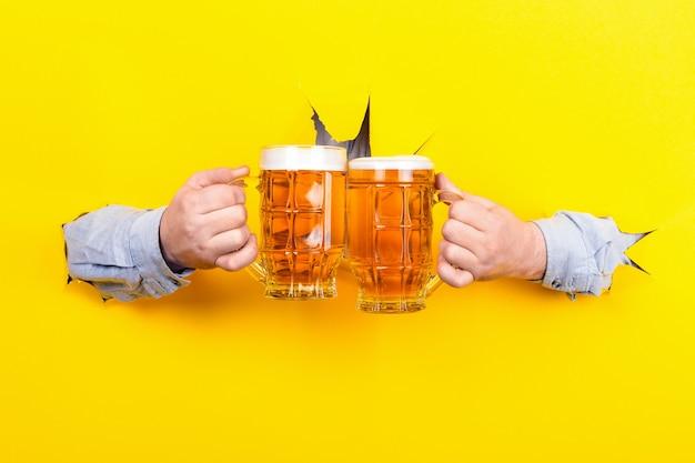 Чокнуться с пивом на желтом фоне Premium Фотографии