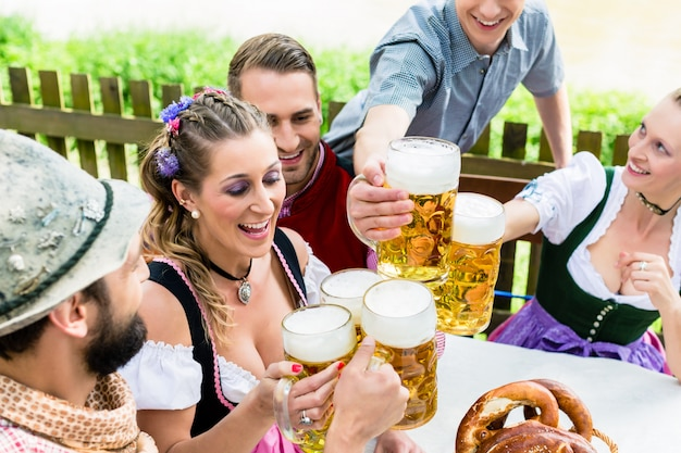 Clinking glasses with beer in bavarian pub Premium Photo