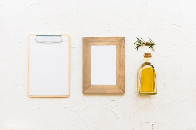 Clipboard and wooden frame with oil bottle and rosemary herb Photo ...