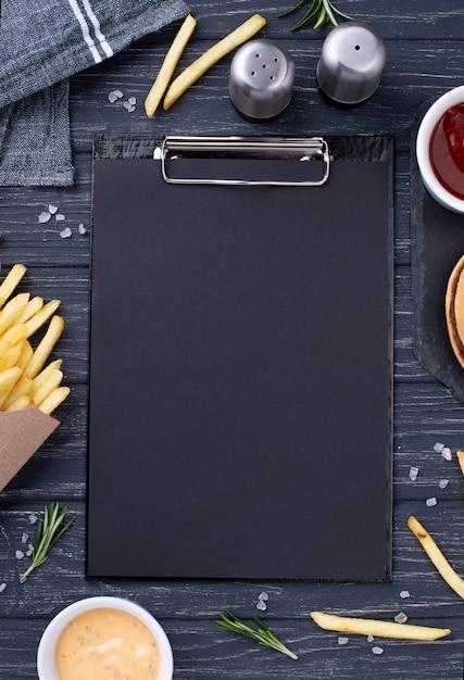 Clipboard beside tasty hamburger with fries Premium Photo