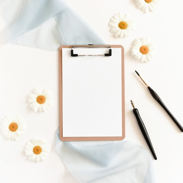 Clipboard, calligraphic pen, paint brush, chamomile flowers on a white background Premium Photo