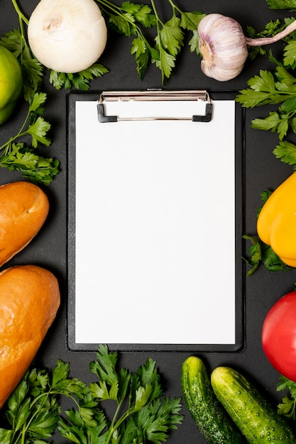 Clipboard mock-up surrounded by fresh veggies Free Photo