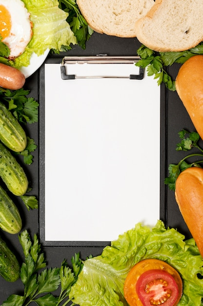 Clipboard mock-up surrounded by vegetables Free Photo