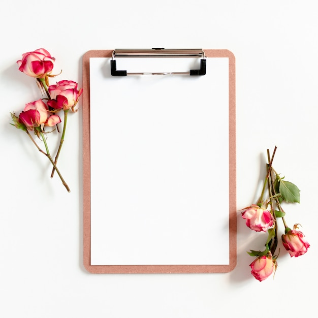 Clipboard mockup and pink roses on a white background Premium Photo