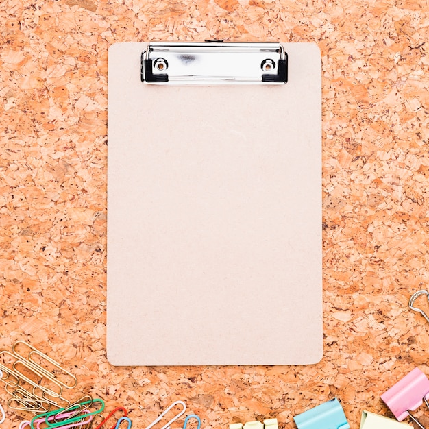 Clipboard and multicolored paper clips placed on cork board Free Photo