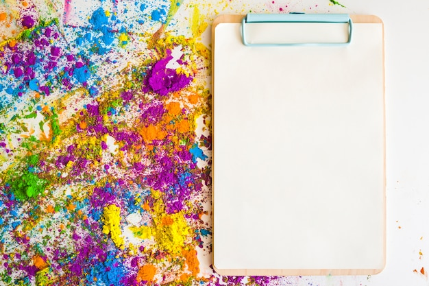 Clipboard near blurs and heaps of different bright dry colors Free Photo