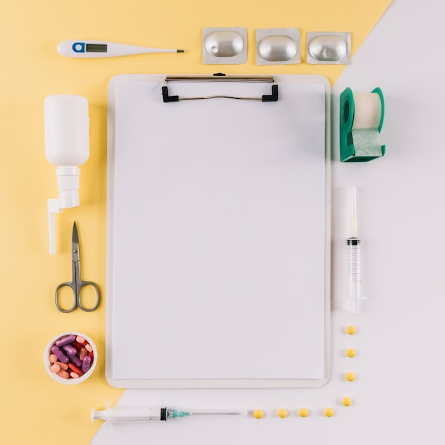 Clipboard with blank white paper surrounded by medical equipments on dual colored background Free Photo
