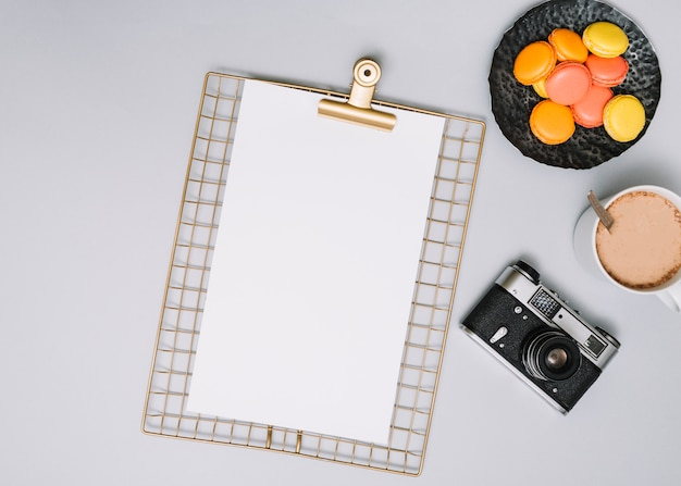 Clipboard with camera, cookies and coffee Free Photo