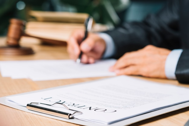 Clipboard with contract papers over wooden desk in courtroom Free Photo