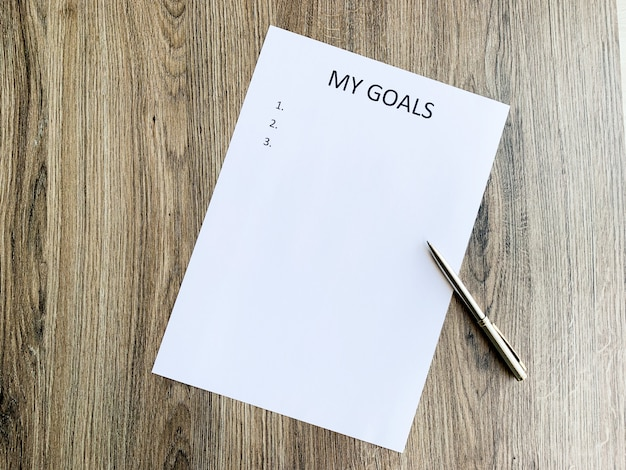 Clipboard with my goals on wood desk. Premium Photo