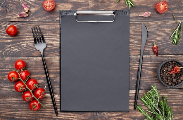 Clipboard with tomatoes and cutlery Free Photo